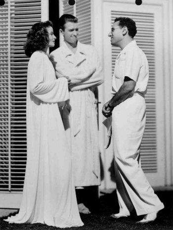 Hepburn and Stewart on set with director George Cukor.