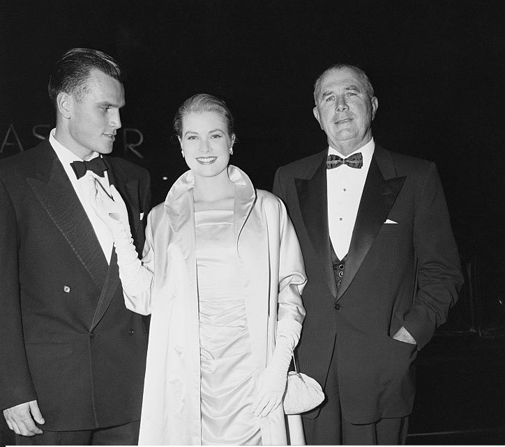 Grace Kelly arrives at the premiere of The Country Girl with her brother Jack Kelly and father John B. Kelly.